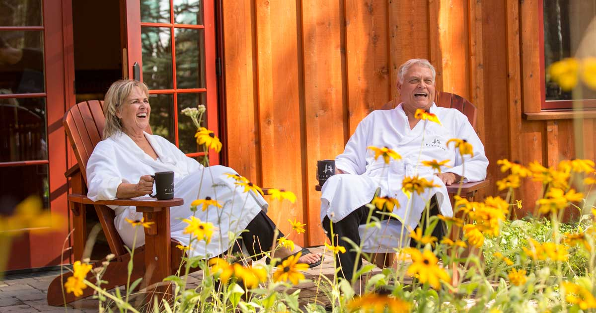A couple wearing spa robes laughs as they drink coffee outside.