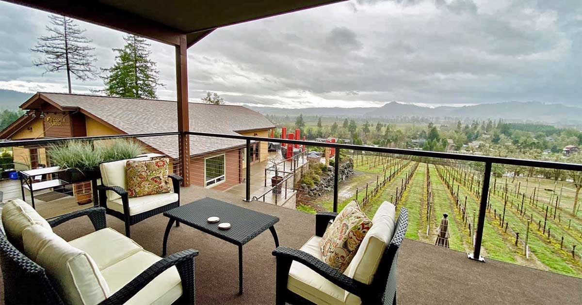 A deck with a table and chairs overlooks the vineyard.