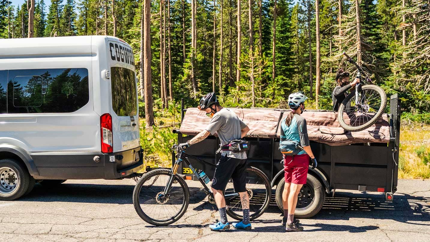 Masked cyclists grab their bikes off a shuttle truck.