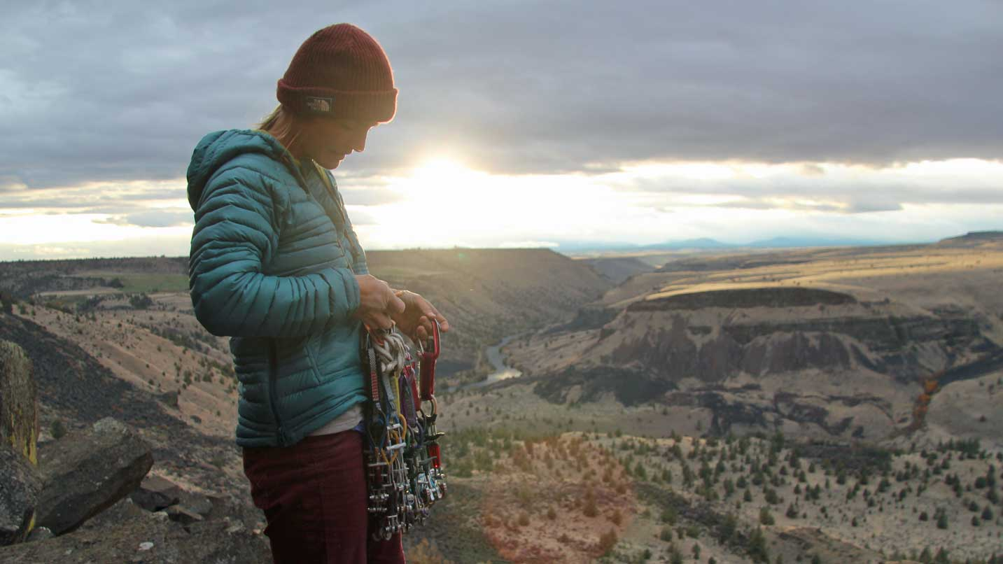 A woman looks at her climbing gear from a vista.