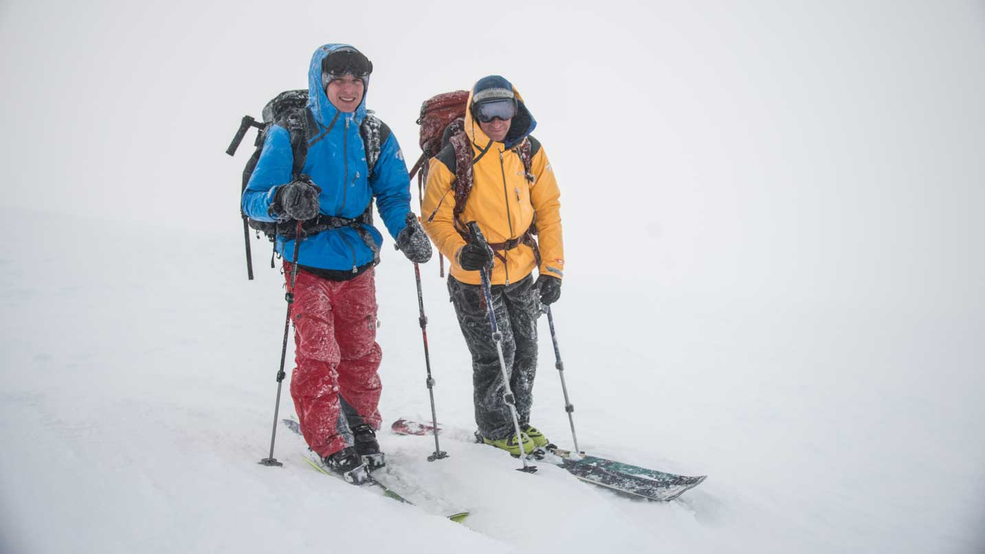 Two people on skis in a winter storm.