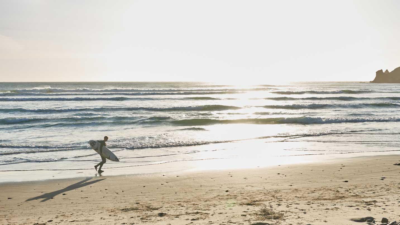 A surfer walks their board along the beach.