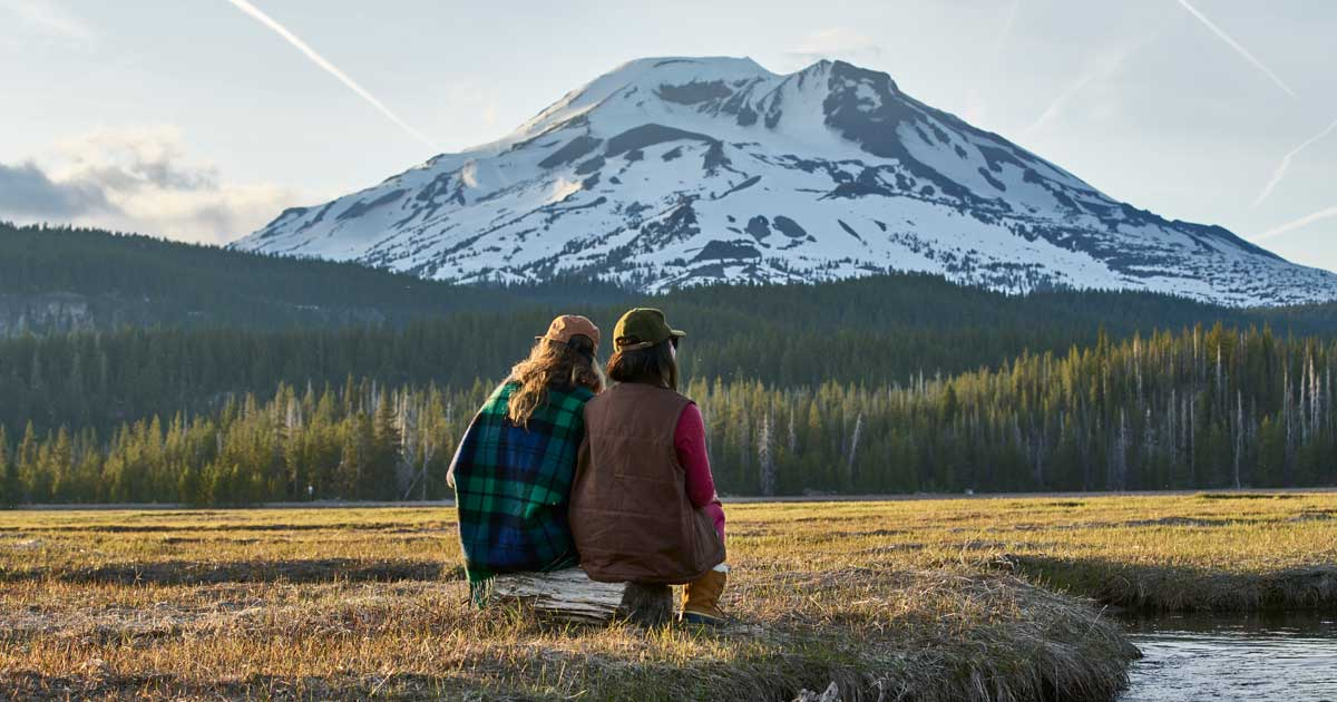 Two people look at a snowy mountain.