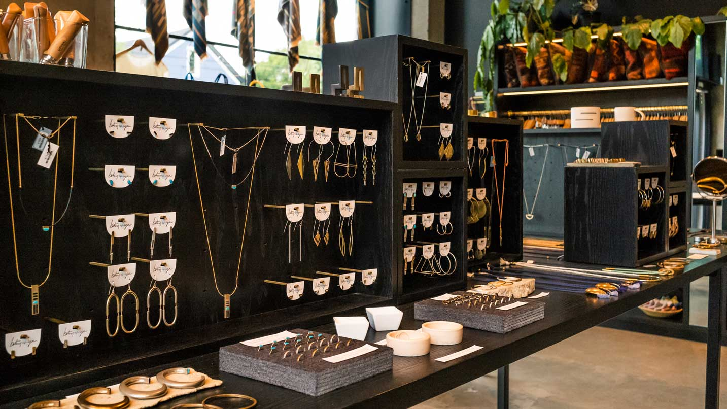 Brass necklaces hang from a display.