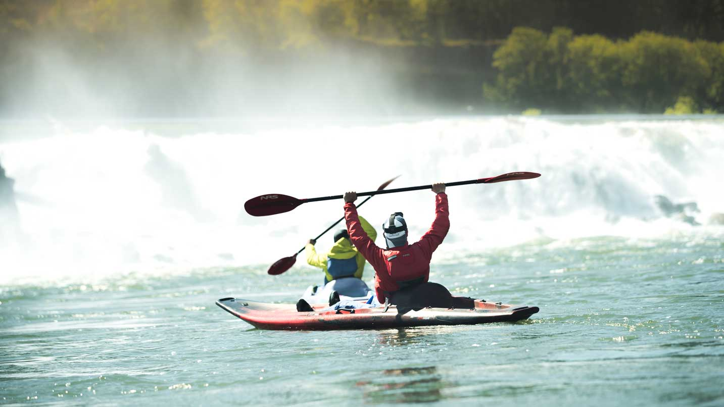 Two kayakers raise their paddles in front of a waterfall.