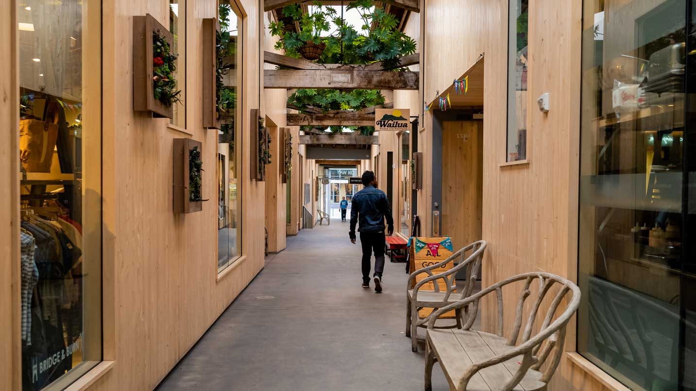 A person walks down a covered walkway next to stores.