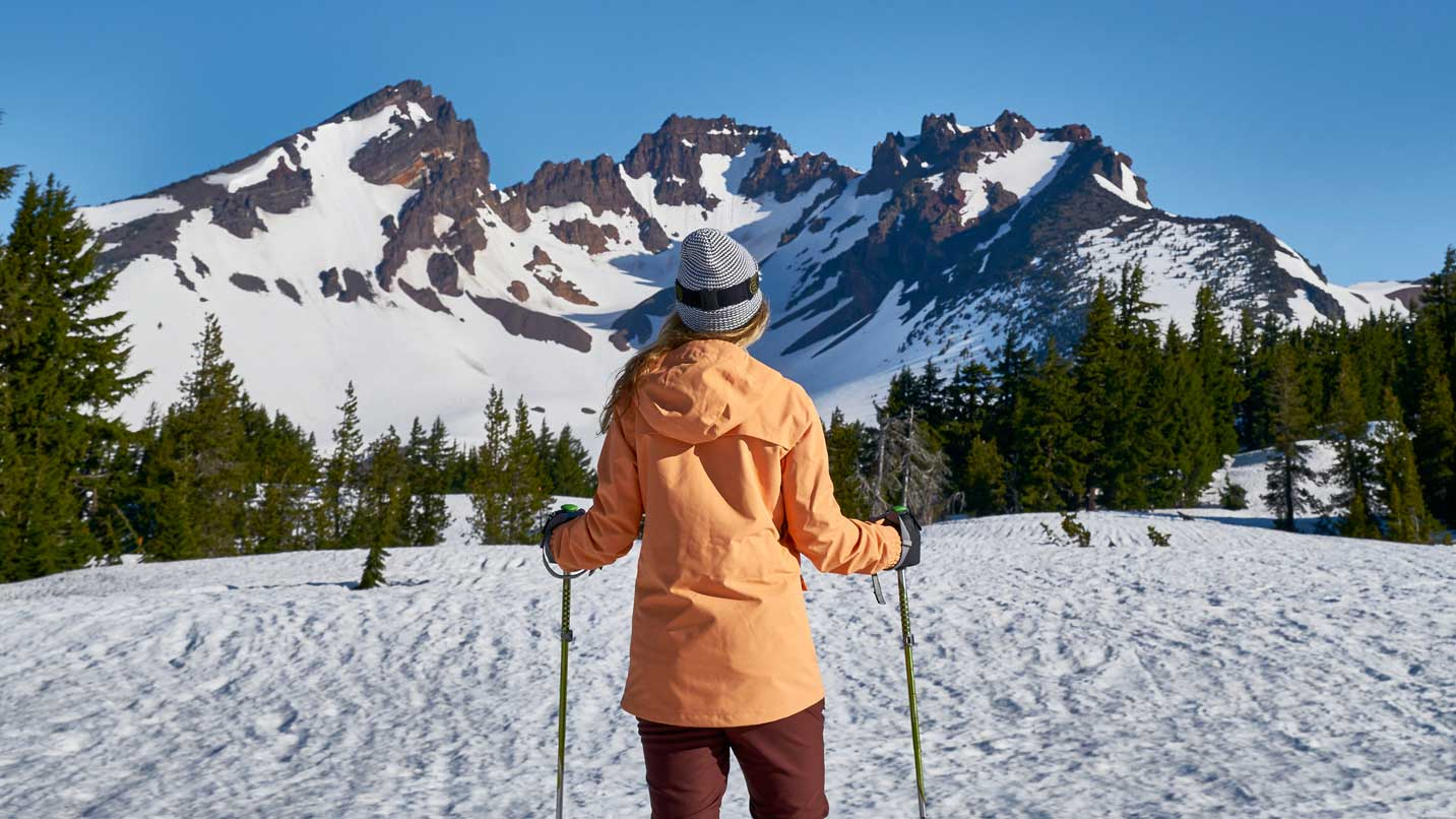 A snowshoer grips their poles as they gaze at a snowy mountain in Central Oregon.