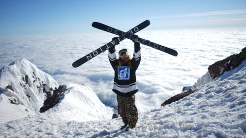 An athlete holds two skis over their head at the top of a snowy mountain.