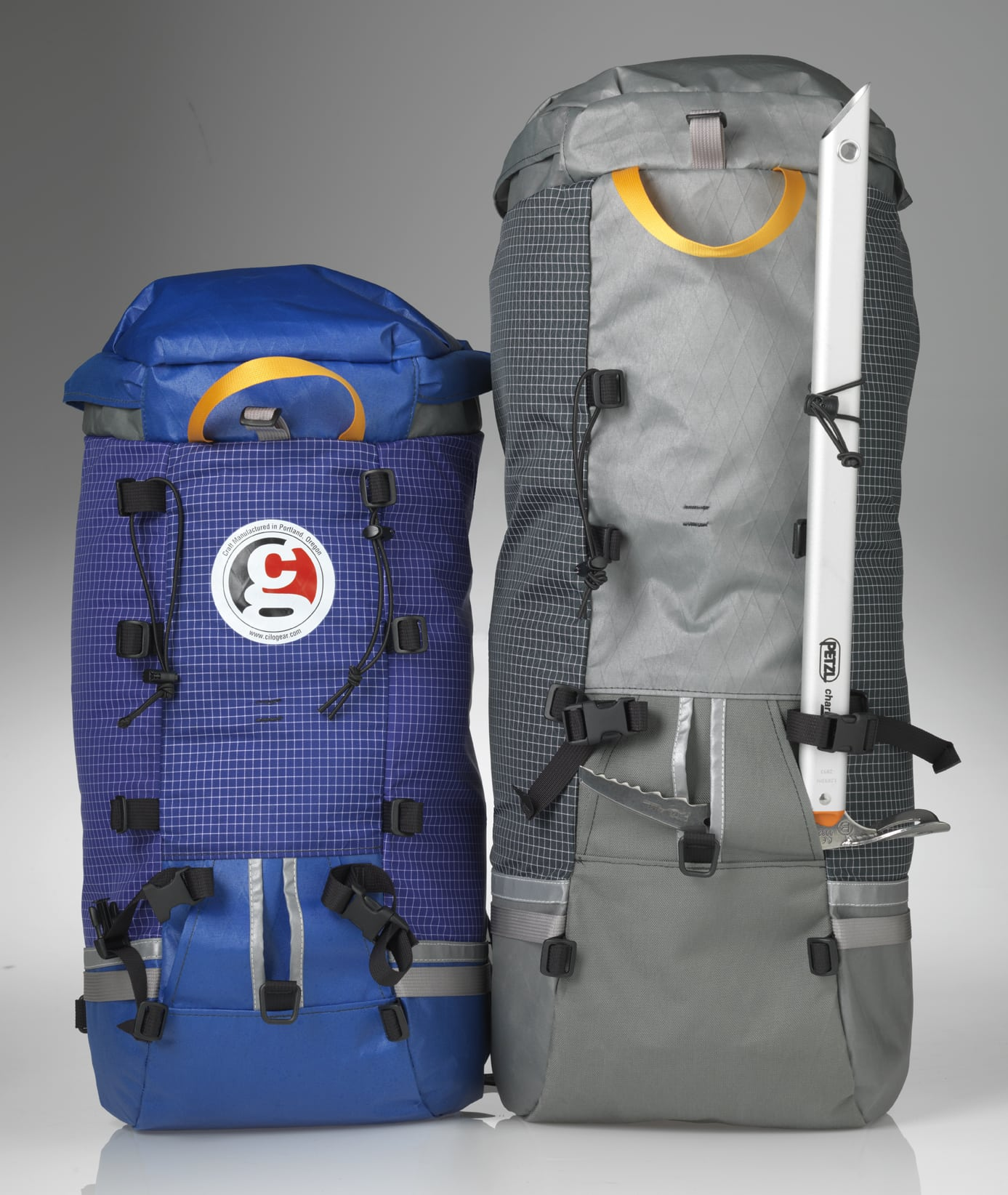 Two ski packs, one smaller and blue and one larger and gray.