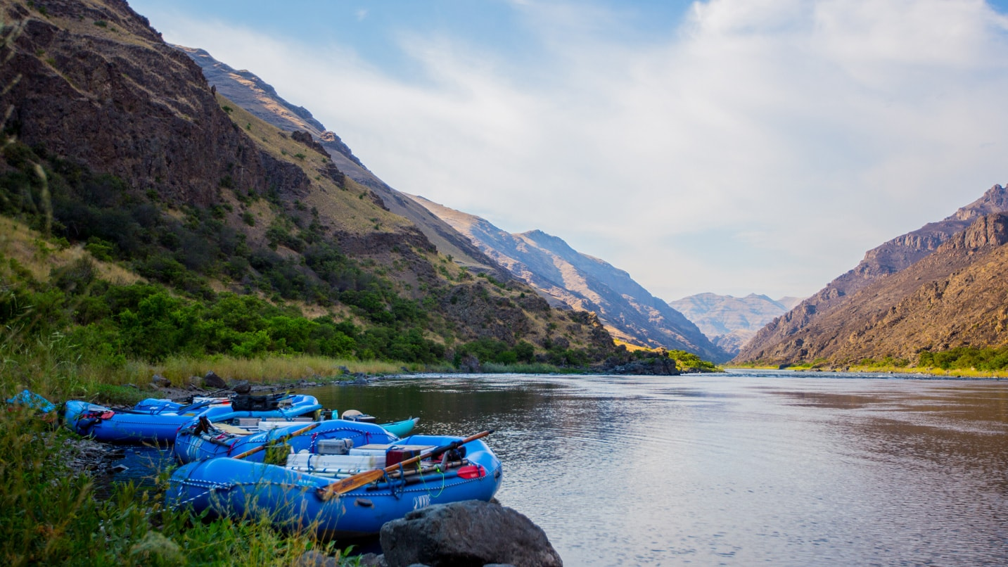 Two rafts sit on the banks of a scenic river.