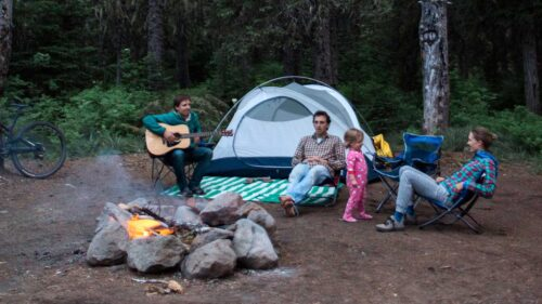 A family sits around a fire at a campsite.