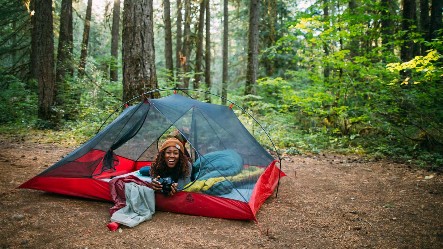 A girl smiles from her pitched tent.