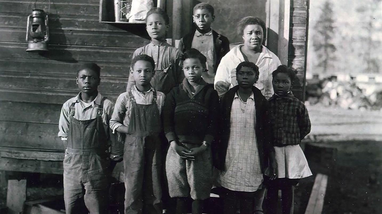 A black and white photo of schoolchildren in overalls.