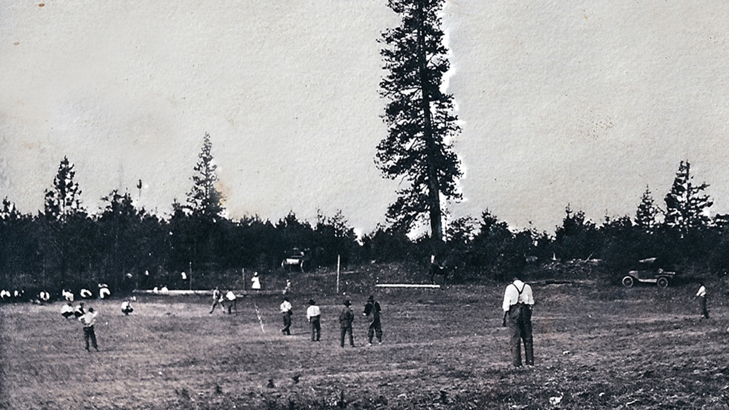 A black and white photo of loggers playing baseball.
