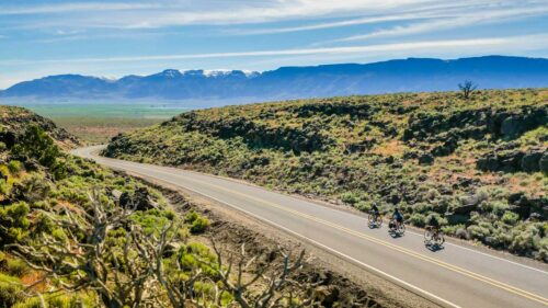 A drone view of three people cycling down a remote road.