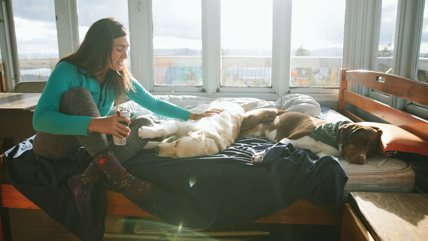 A girl pets her dog inside a fire lookout cabin.