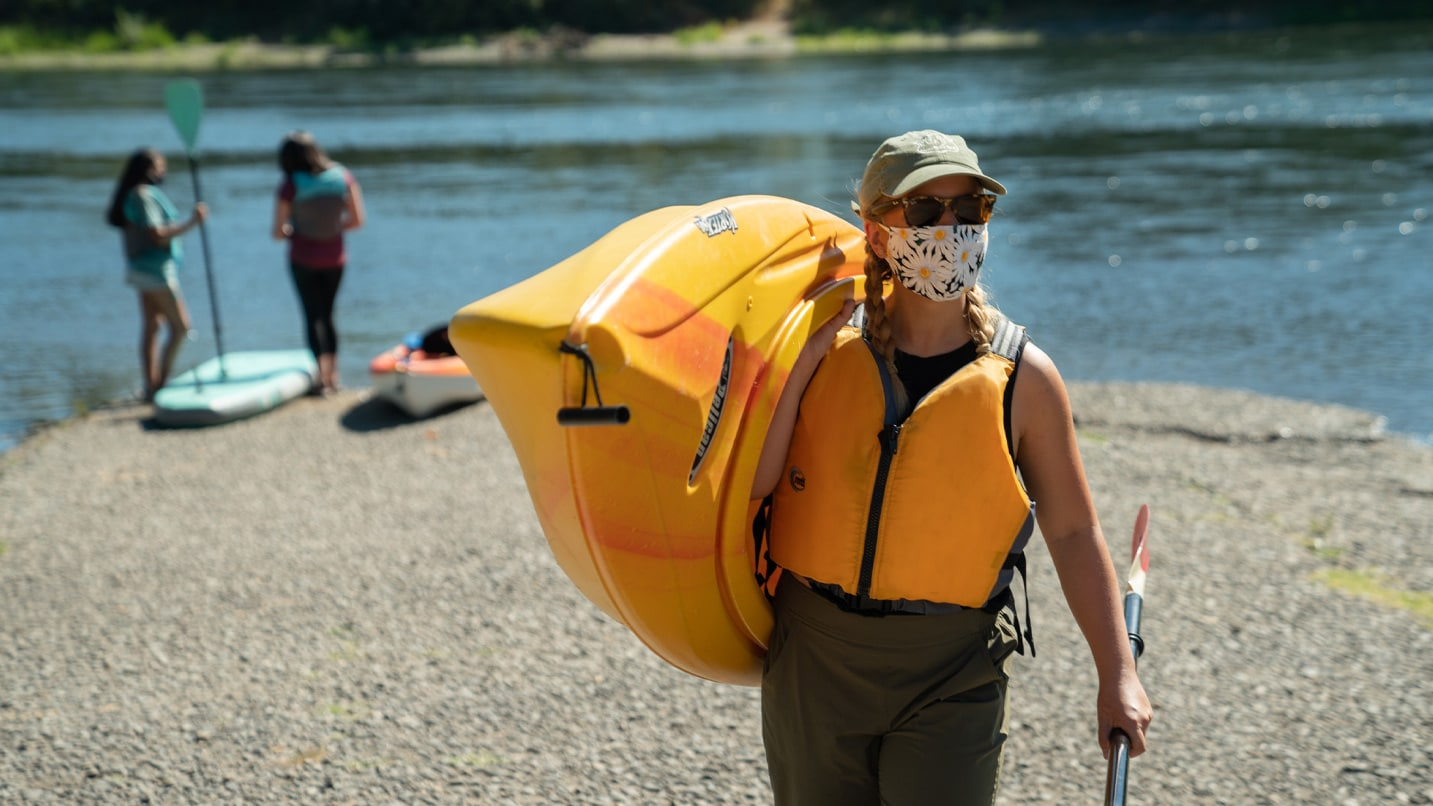 A masked person carries a kayak next to the river.