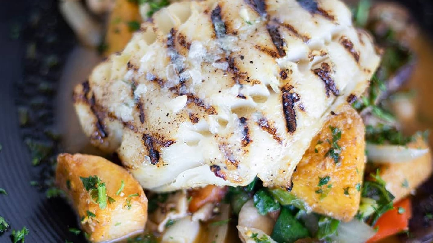 A grilled fish filet sits on a bed of vegetables.