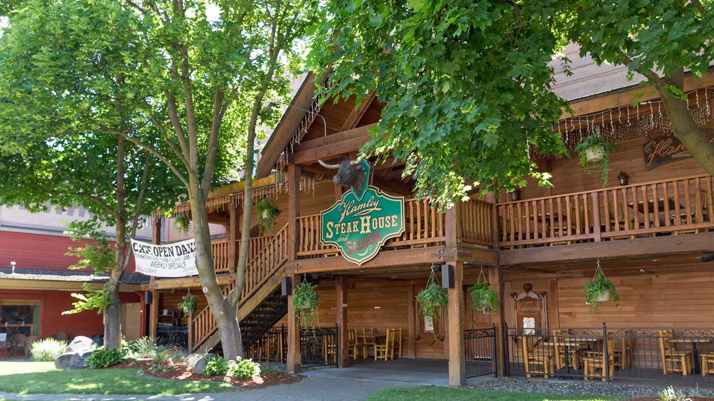 The exterior of Hamley Steakhouse reveals a two-story wooden structure surrounded by trees.