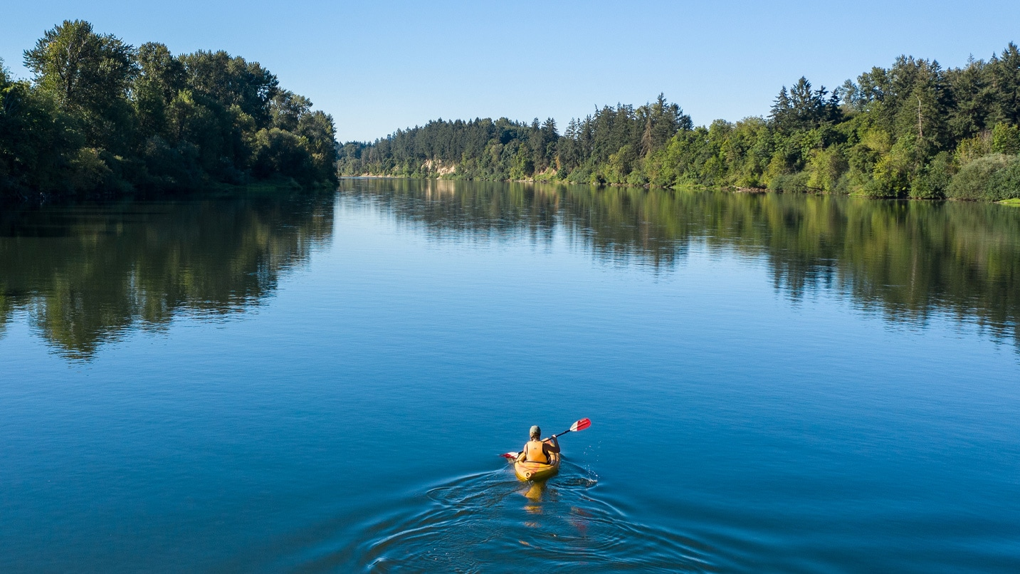 A kayaker leaves ripples in the glassy waters of the Willamette.