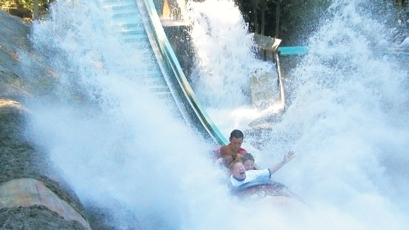 People get wet as the log ride splashes into water.