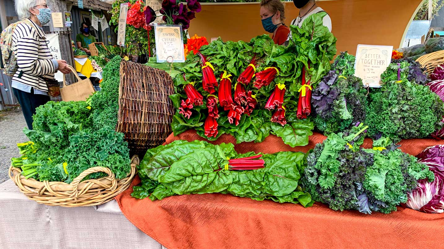 Masked people peruse vegetables at a farmer's market.
