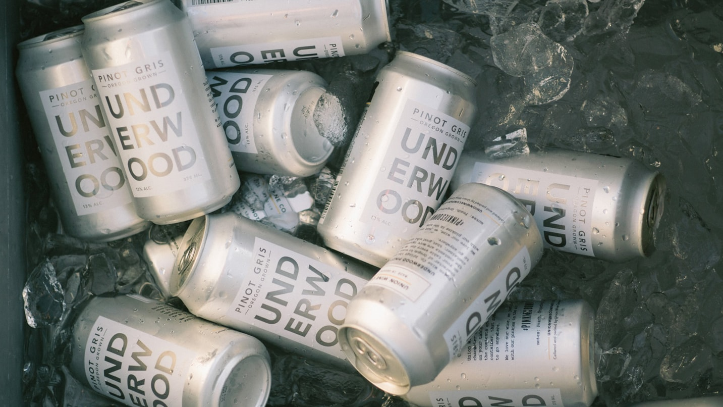 Silver cans of Underwood pinot gris sit in ice.