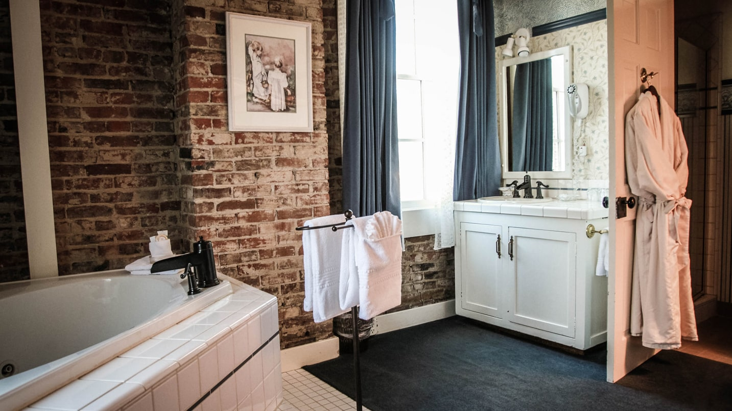 Porcelain bathroom fixtures are set in front of a brick wall and navy-blue accents.