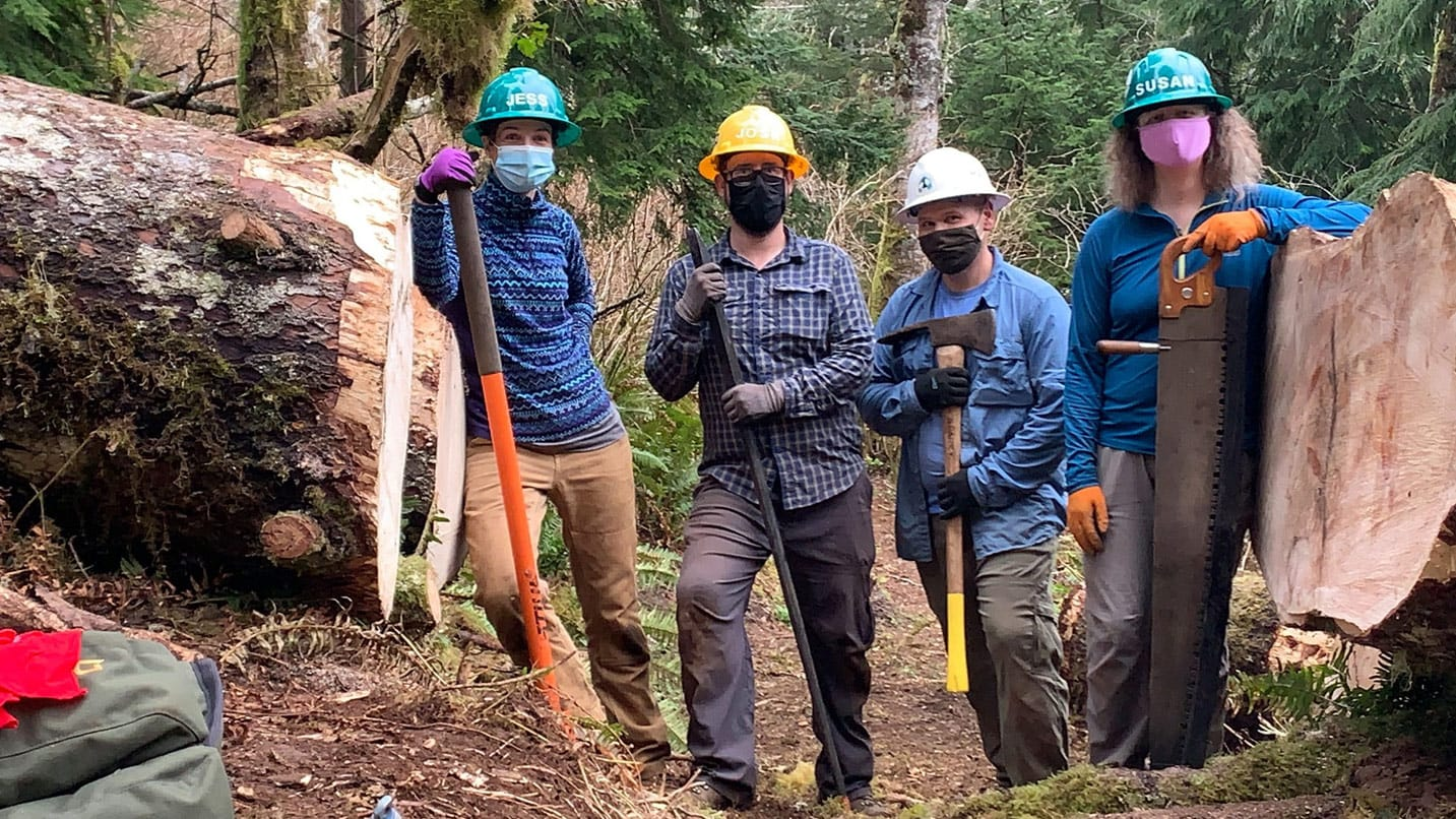 Four people wear masks and hard hats at a trail.