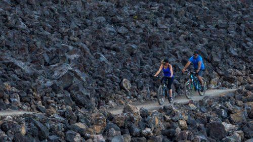Two people bike on a trail through lava rocks