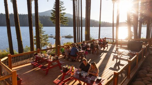 Scenic view of people on a restaurant deck overlooking a lake