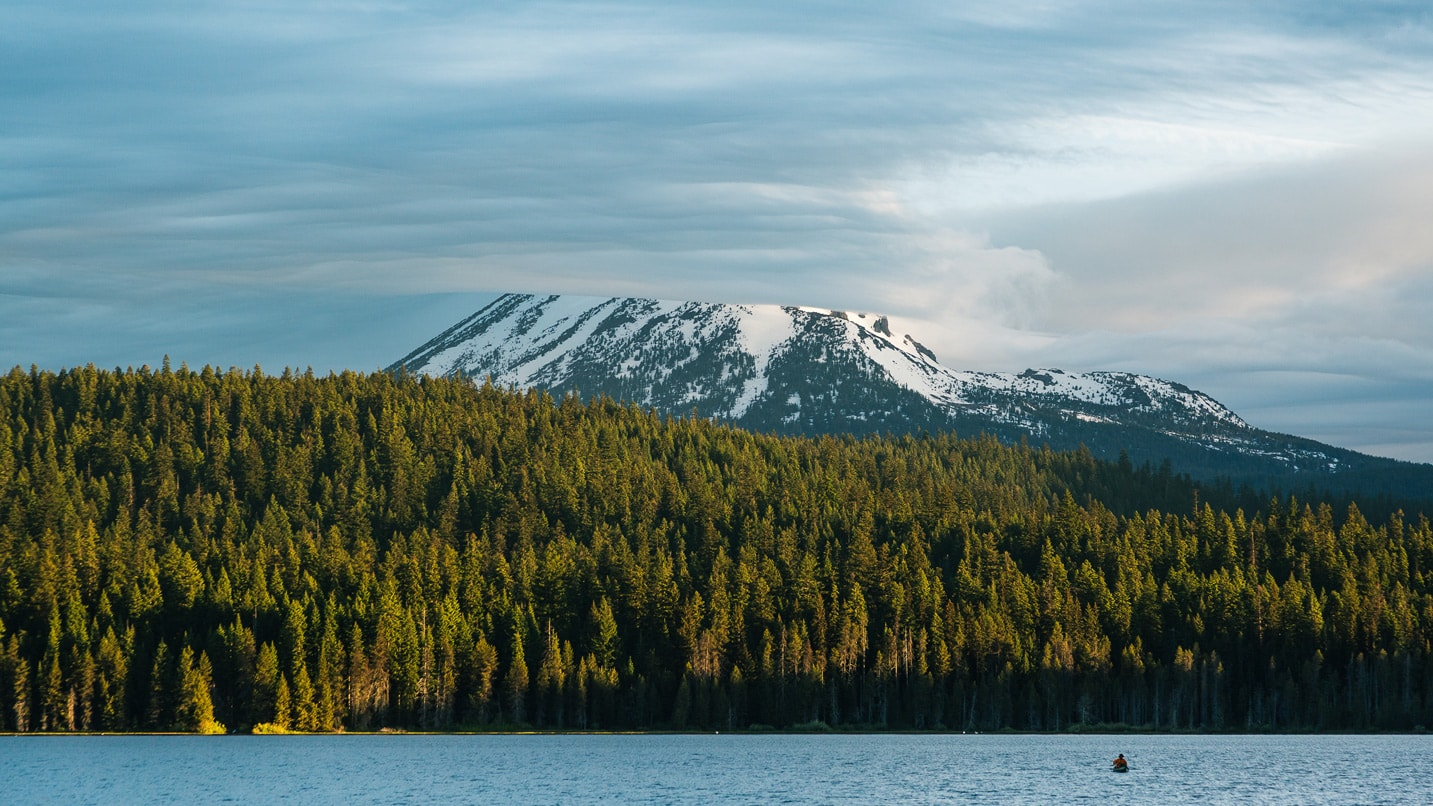 Trees line the water in front of a snow-capped peak.