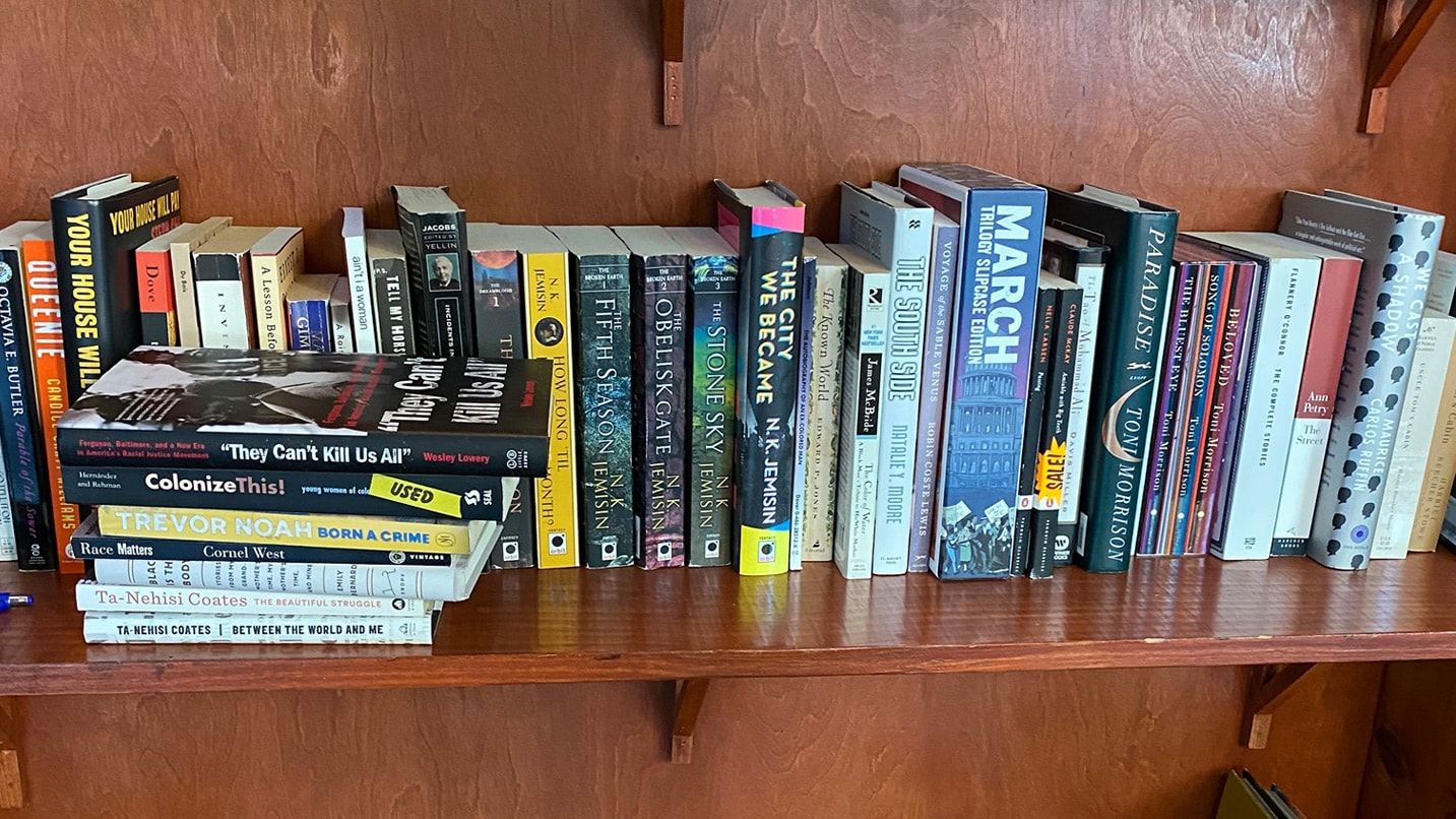 Books pile on a wooden shelf.