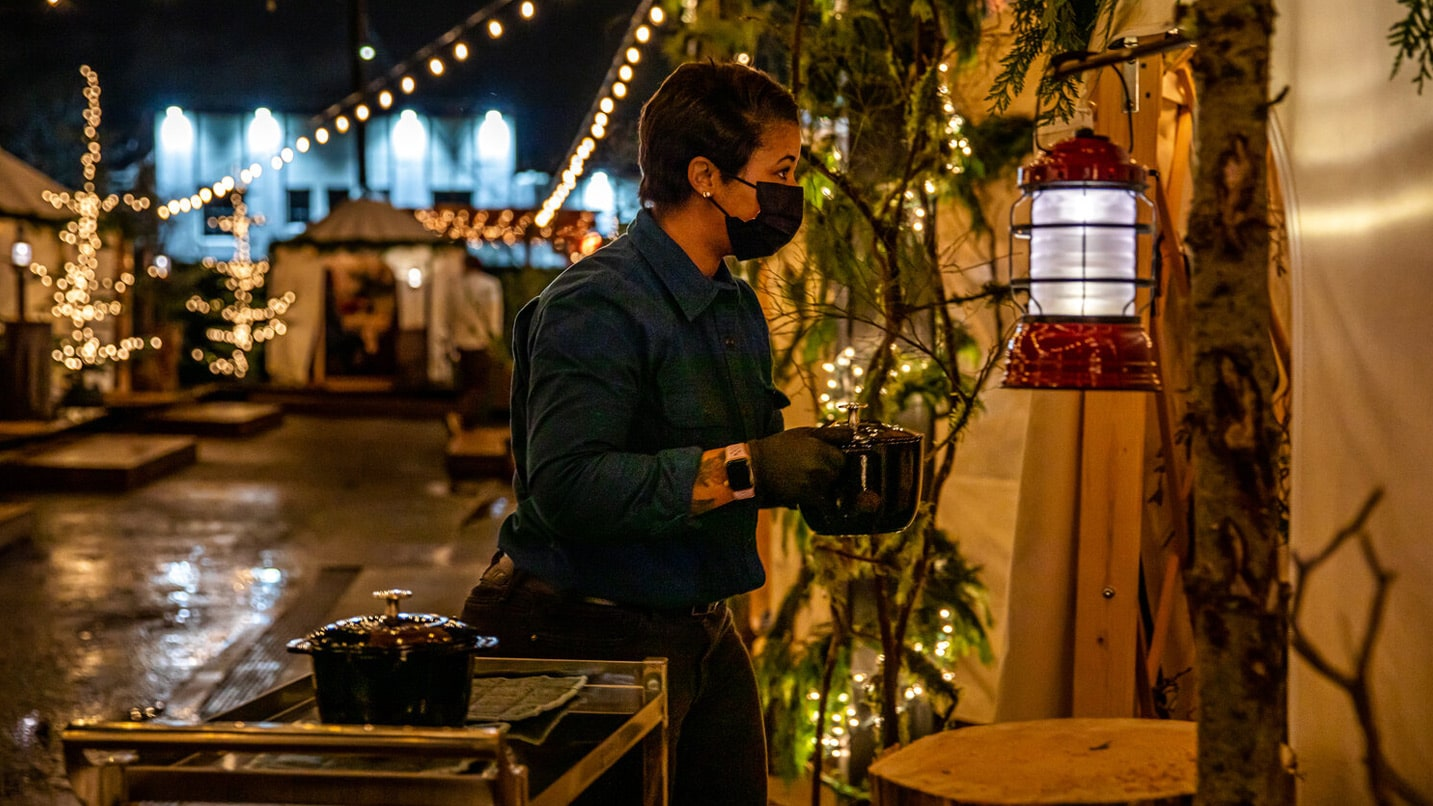 A masked server brings hot food into a yurt decorated in vines and lights.
