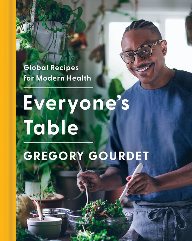 """The cover of """"Everyone's Table"""" cookbook features Gourdet tossing a salad and smiling."""