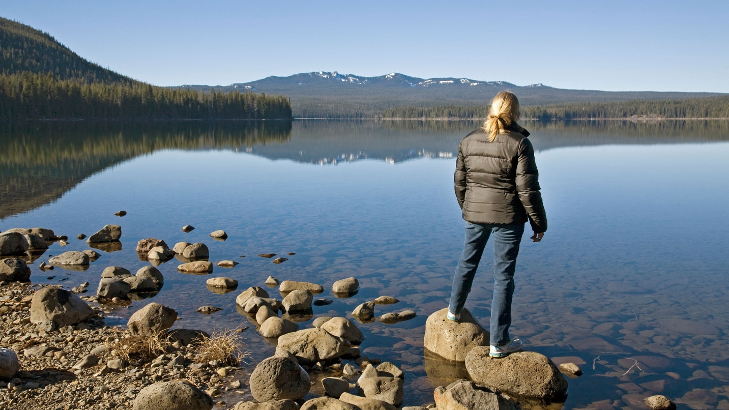 A woman standing on a rock at the edge of a lake