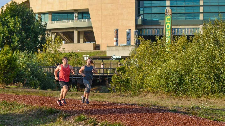 Two runners jog past Autzen Stadium.