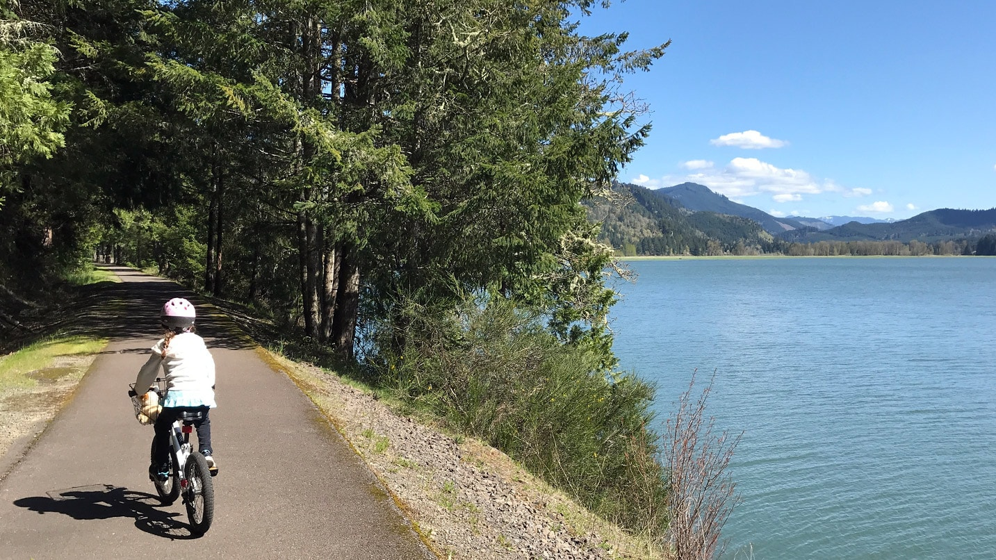 A young cyclist pedals past a lake to a tree-covered path.