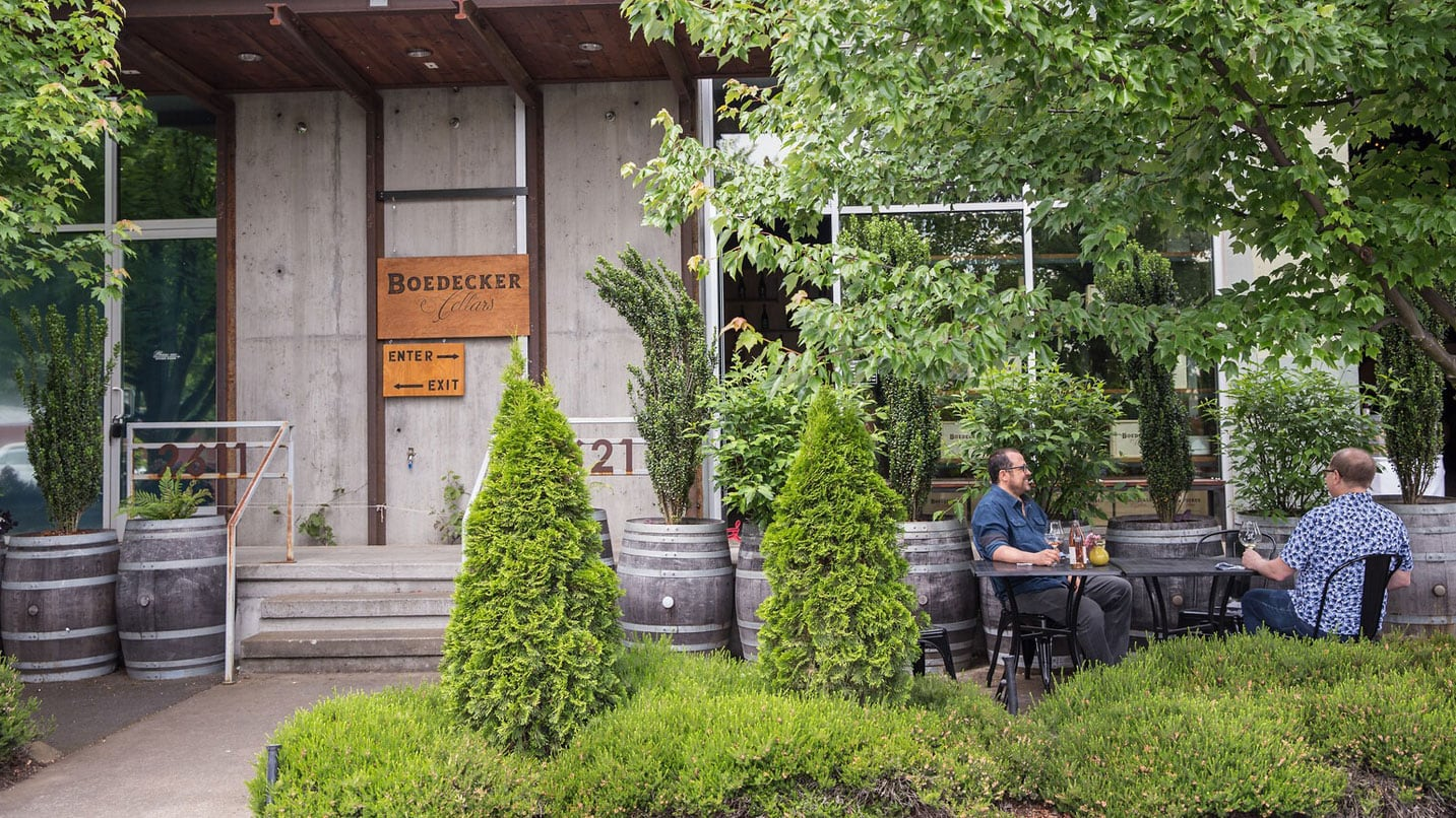 Two people taste wine in front a building surrounded by shrubs.