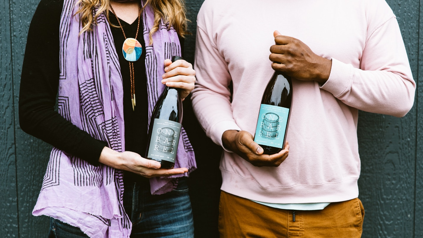 Two people hold bottles of wine.