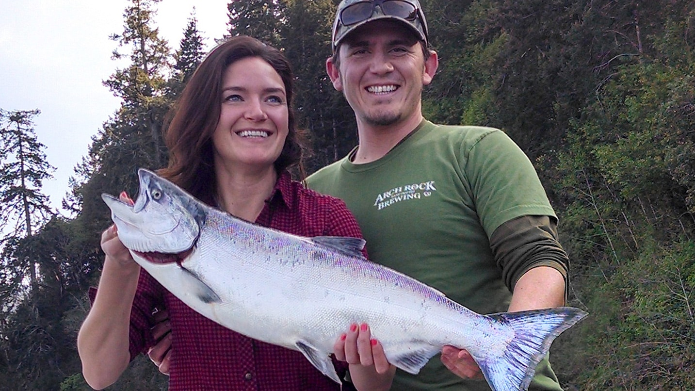 Two people hold a large chinook fish
