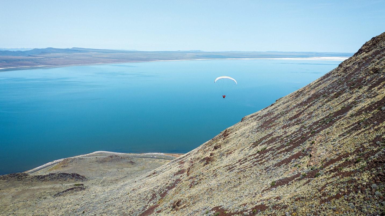 A paraglider sails over Lake Abert