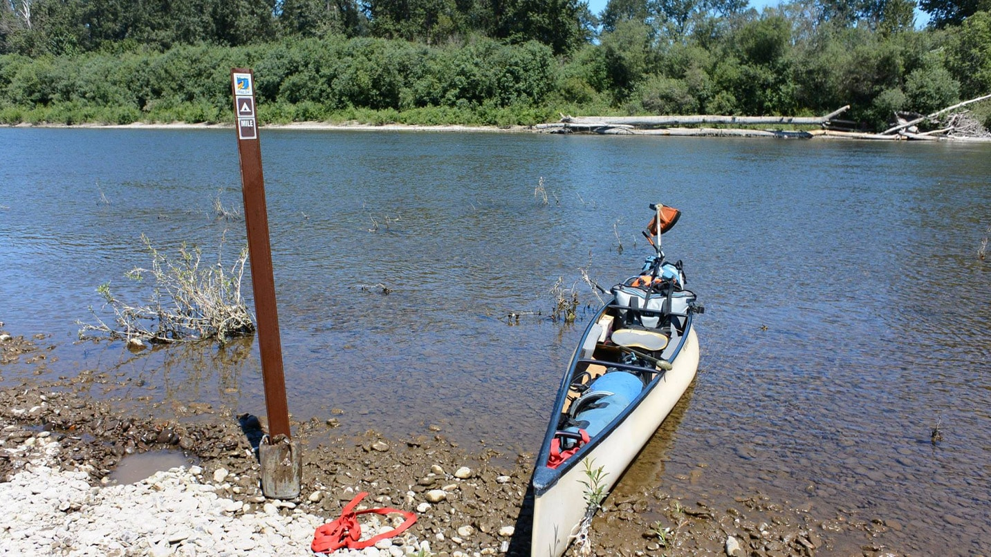 A canoe loaded with camping gear pulled ashore