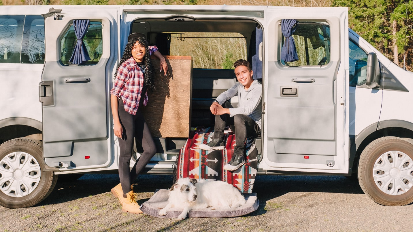 The author, her partner and their dog pose in front of their van