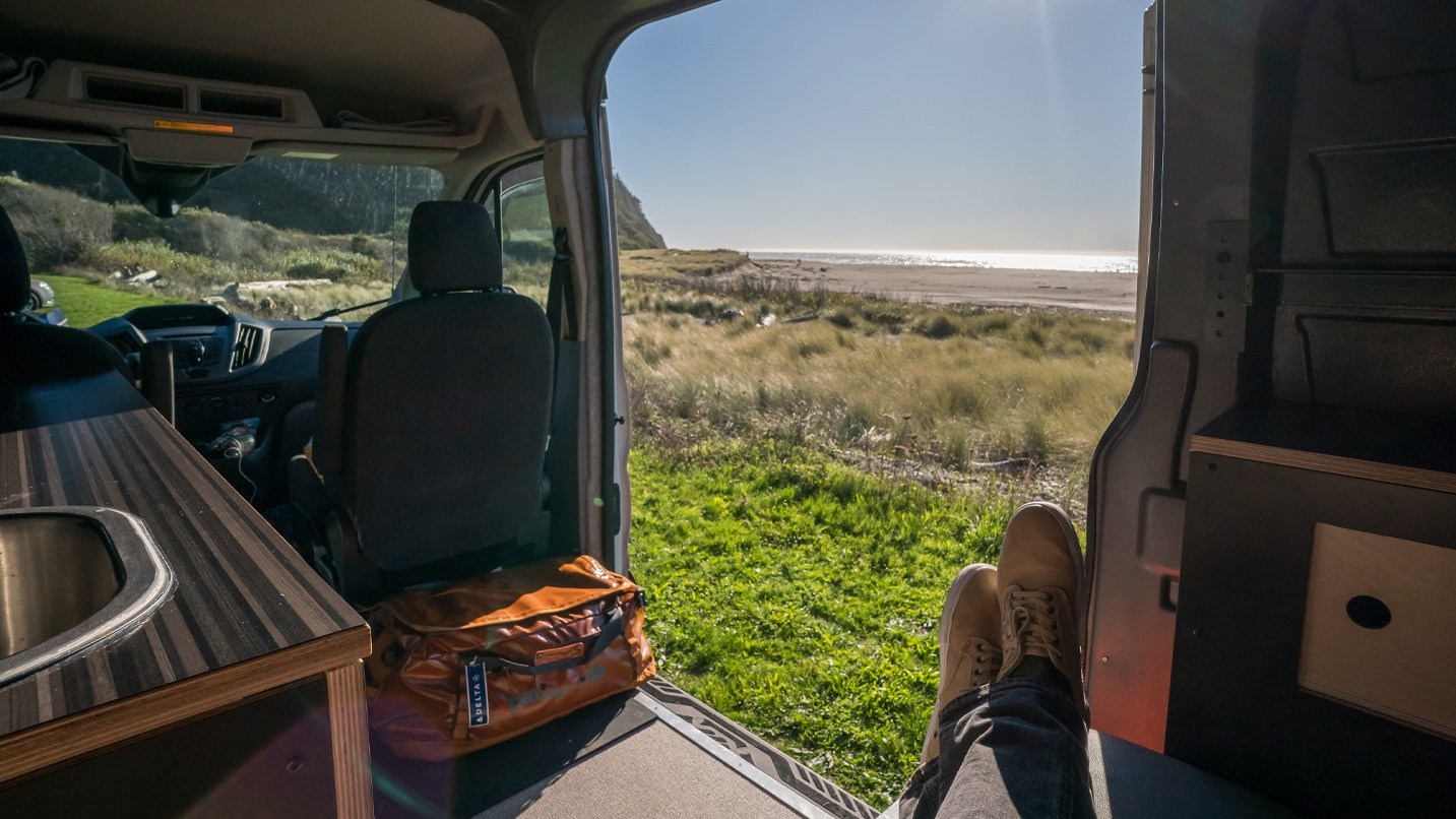 Inside of a campervan with the ocean in the distance