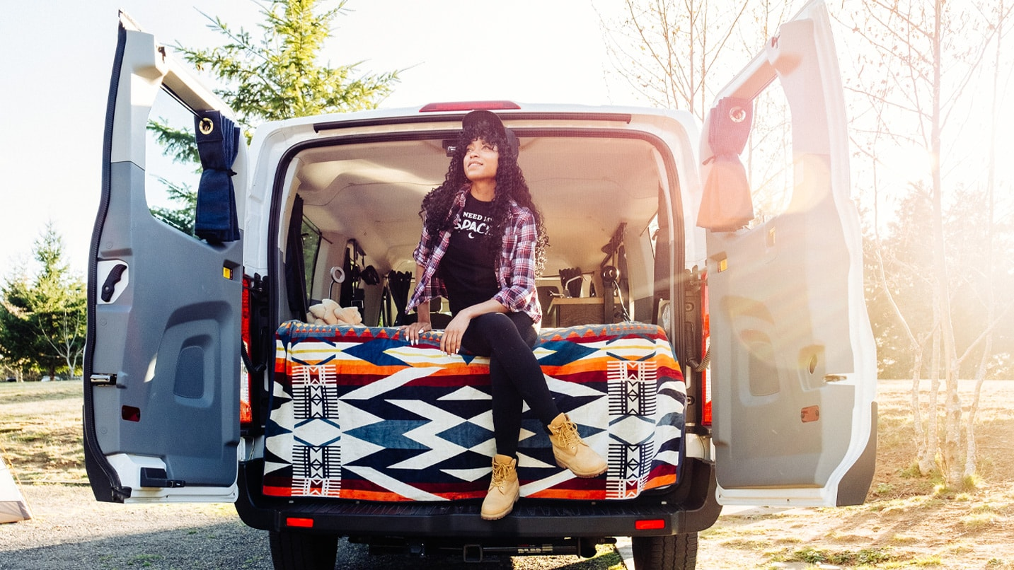 The author sitting on a Pendleton blanket looking out of the back of her campervan