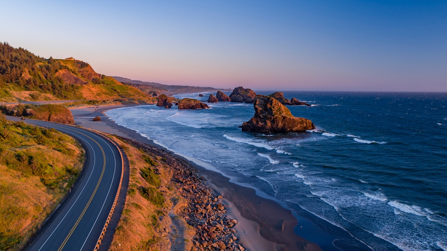 Scenic aerial view of the highway and Pacific Ocean at sunset