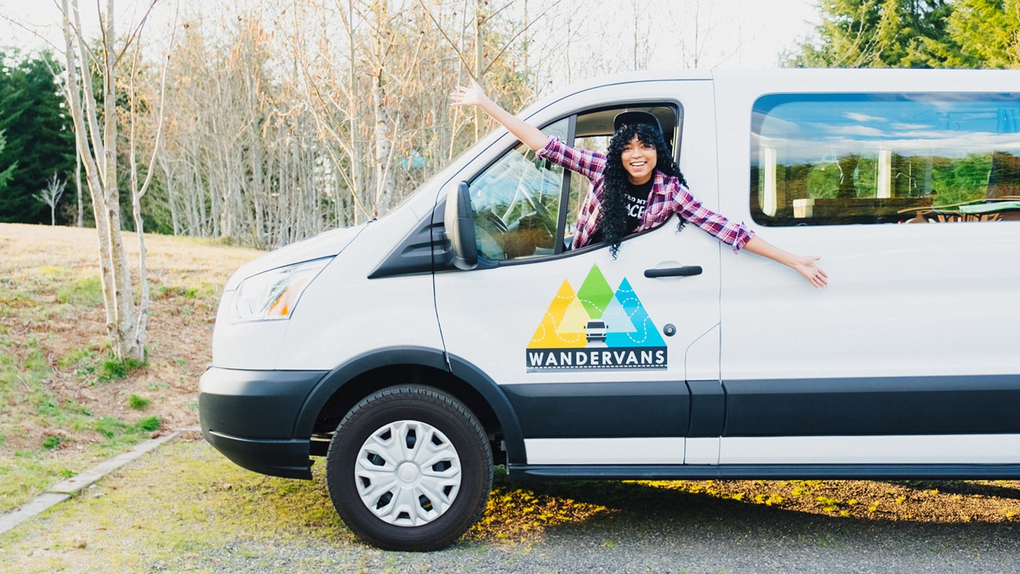 A woman leans out of a parked campervan