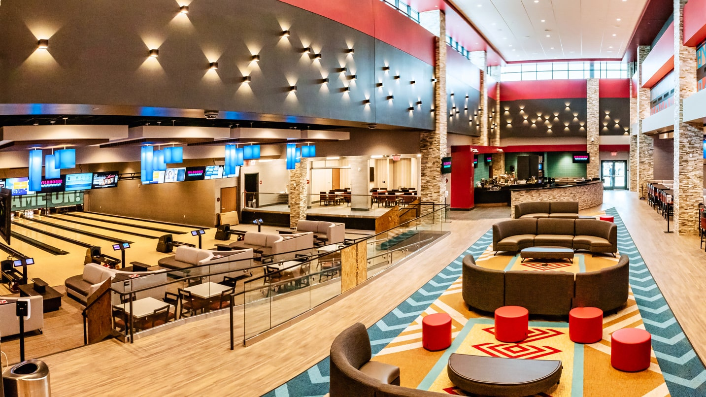 A panoramic interior view showing bowling lanes and a lounge area