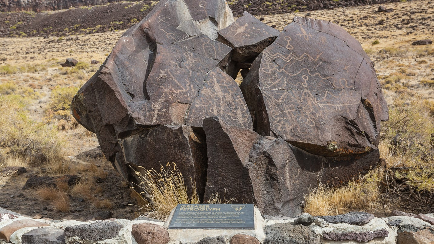 A plaque in front of petroglyphs carved on a rock